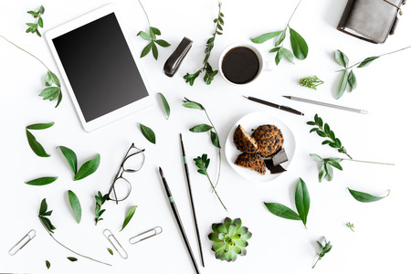 흰색으로 격리 디지털 타블렛, 쿠키 및 사무 용품의 상위 뷰