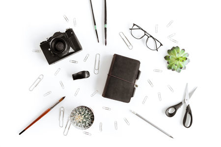 Top view of wallet, camera and various office supplies and plant
