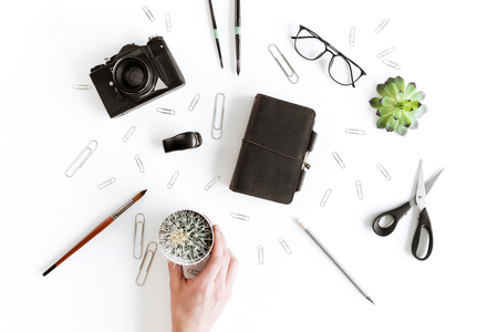 Partial top view of human hand holding cactus and various office supplies and plant