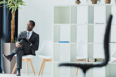 pensive african american businessman sitting on chair in office and looking away