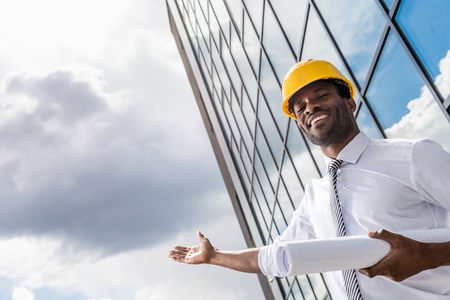 smiling architect in hard hat holding blueprint and gesturing
