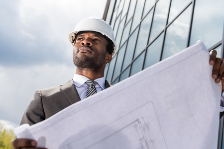 professional architect in hard hat holding blueprint outside modern building