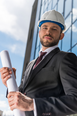architect in hard hat holding blueprint and looking at camera