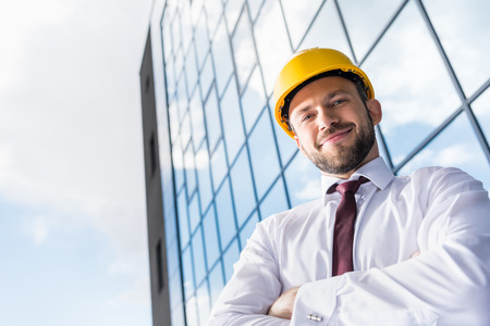 smiling professional architect in hard hat against building Banco de Imagens