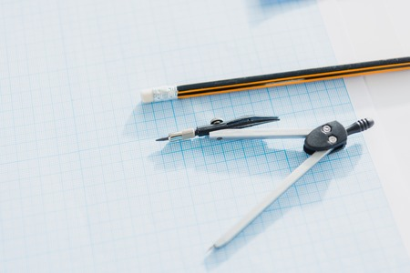 close up of office compasses and pencil lying on empty blueprint