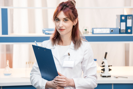 scientist in lab coat holding folder and looking at camera in chemical lab
