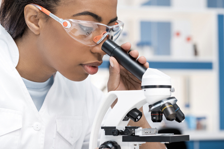 african american scientist in lab coat working with microscope in chemical lab