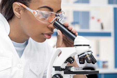 Scienziato africano americano in laboratorio cappotto che lavora con microscopio in laboratorio chimico Archivio Fotografico - 80156946