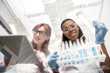 scientists working together with reagents in laboratory Stock Photo