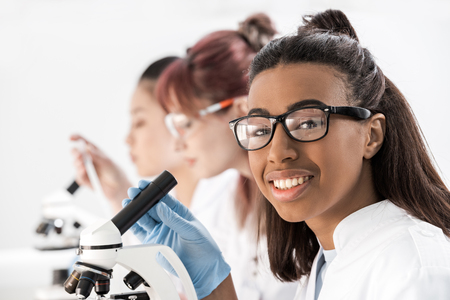 化学研究室で顕微鏡を操作若い専門の科学者のグループ 写真素材