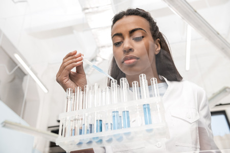 young scientist working with test tubes and reagents in chemical lab