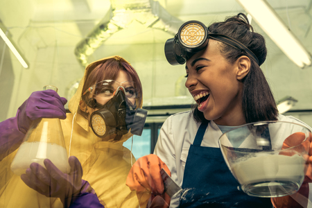 portrait of woman dividing drugs with friend holding flask near by in laboratory Stock fotó