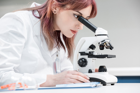 scientist in lab coat working with microscope in chemical lab