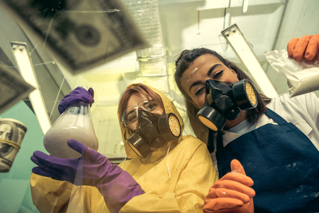 two young women chemists working at scientific laboratory with drugs
