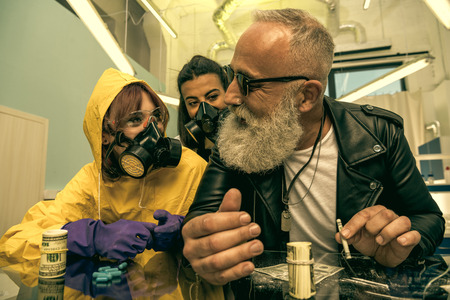 grey hair man with beard taking drugs with women in personal protective equipment