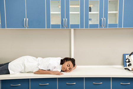 tired girl scientist sleeping on table in chemical laboratory, chemical lab