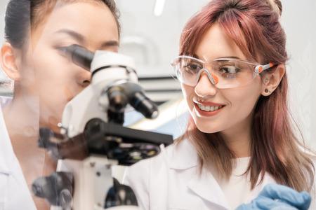 poblíž: žena vědec pohledu přes mikroskop s kolegy v blízkosti