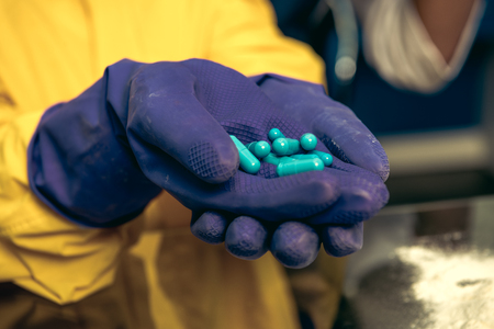 hands in rubber gloves holding pills in laboratory, chemical lab