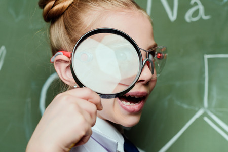 grimace little girl with magnifying glass with chalkboard behind Imagens