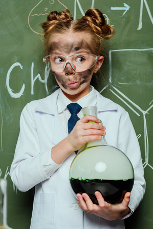 white coat holding flask with chalkboard behind in science laboratory