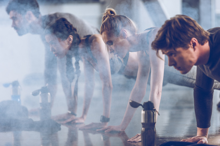 group of athletic young people in sportswear doing push ups or plank at the gym Reklamní fotografie - 80157769