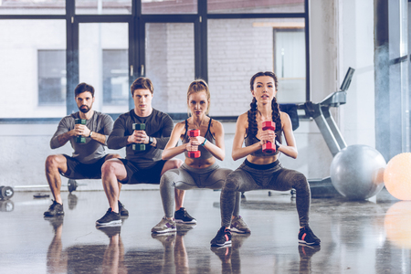 athletic young people in sportswear with dumbbells exercising at the gym Reklamní fotografie