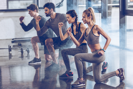 group of athletic young people in sportswear doing lunge exercise at the gym