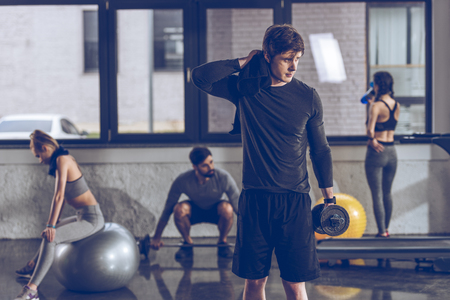 partial: athletic tired sportsman with dumbbell at the gym