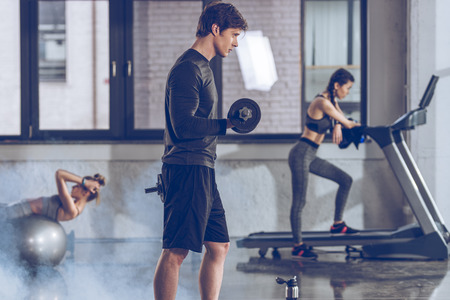 athletic young sportsman exercising with dumbbell at the gym