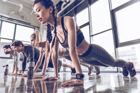 groep van atletische jongeren in sportkleding doet push ups of plank in de sportschool