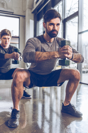 young men in sportswear with dumbbells exercising at the gym Stock Photo