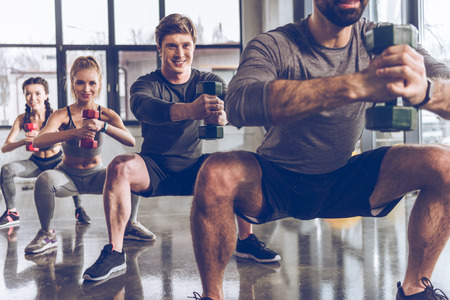 athletic young people in sportswear with dumbbells exercising at the gym 写真素材