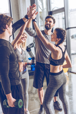 young athletic people in sportswear giving high five in gym