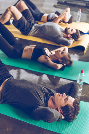 Sporty young people doing abs on yoga mats while exercising
