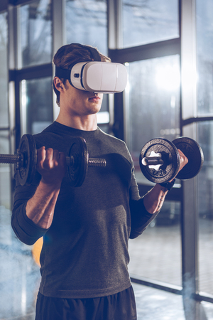 man in virtuele reality headset die met domoren in de sportschool uitoefent