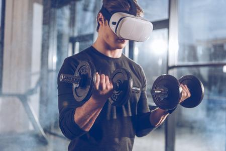 체육관에서 아령으로 운동하는 가상 현실 헤드셋의 남자 스톡 콘텐츠