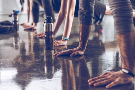 腕立て伏せやジムで板を行うスポーツの運動の若者たちのグループ 写真素材