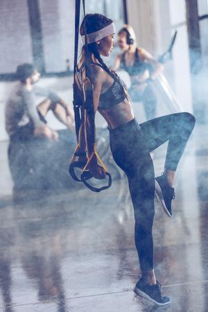 sportieve vrouw die met trx gymnastiekapparatuur uitoefent