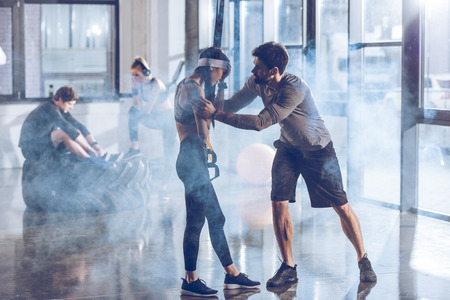 man cheering up sportive woman in gym with trx equipment