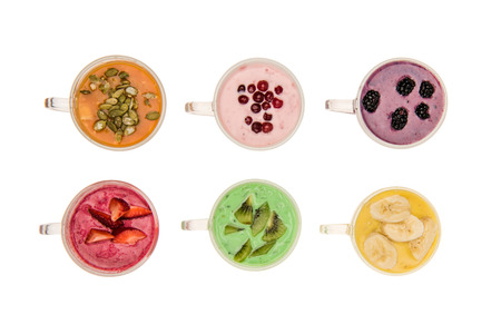 Top view of fresh fruit smoothies in glass cups isolated on white