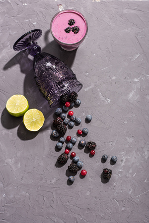 top view of berries smoothie in glass tumbler with blueberries and lime slices, berries smoothie
