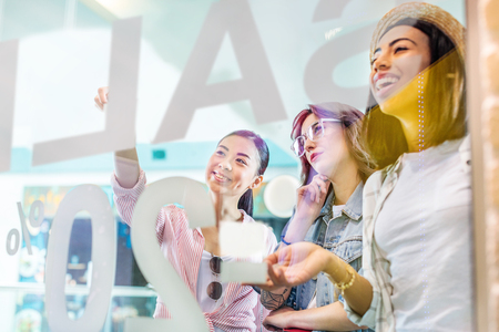 multicultural hipster girls looking at showcase in shopping mall Stock Photo
