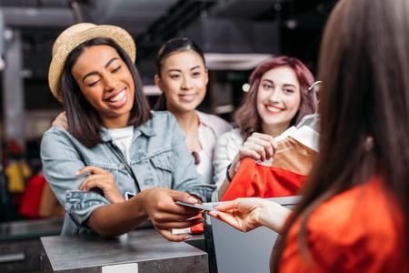 Gelukkige stijlvolle jonge vrouwen die met een creditcard in winkelcentrum betalen Stockfoto