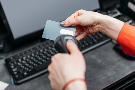Close-up partial view of person using payment terminal and scanning credit card Фото со стока
