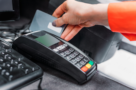 partial: Close-up partial view of person using payment terminal and credit card