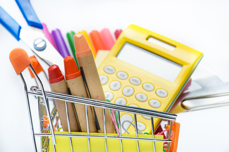 different colorful school supplies in shopping cart