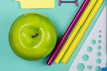 Bovenaanzicht van appel- en viltpennen op kleurrijke tafelblad Stockfoto
