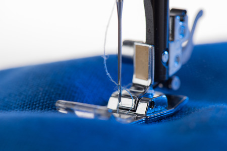 working sewing machine sewing blue fabric