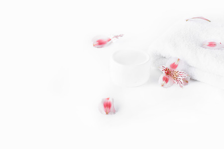natural body cream in container, towel and orchids isolated on white Stock Photo
