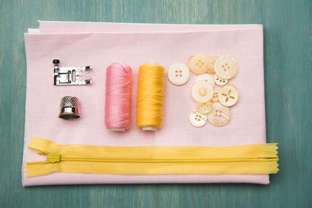 set of various sewing supplies on wooden colorful surface